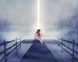 Lonely woman sitting on pier bright glowing light in hand