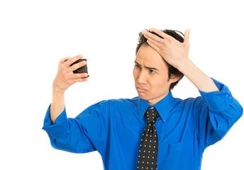 man looking in mirror feeling head surprised shocked losing hair
