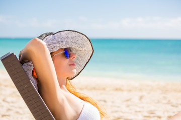 Young woman with sun hat enjoying sea view laying on chair
