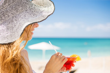 woman with cocktail on the beach enjoying sunny weather