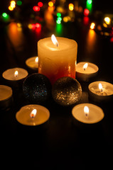 Small candles around a bigger candle and two Christmas globes