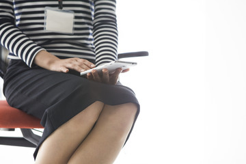 Young woman looking at mobile phone sitting on a chair