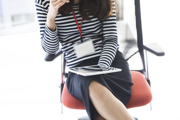 Woman young looking at tablet sitting in a chair