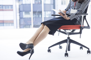 Women who are looking at the tablet sitting in a chair