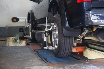 Car on stand with sensors on wheels for wheels alignment camber