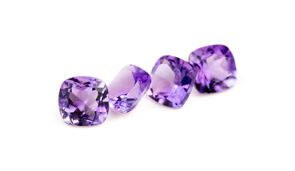 Natural purple amethyst gemstones isolated on white