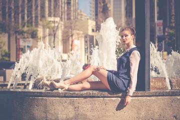 Beautiful young woman in the city near fountain