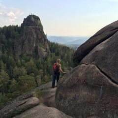 Молодая девушка спортсменка с рюкзаком на скале