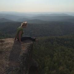 Молодая девушка на скале на фоне гор