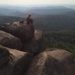 Молодая девушка спортсменка на скале на фоне гор