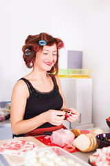 Young pretty woman housewife cooking with curlers on hair