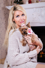 Woman with yorkshire terrier near fireplace