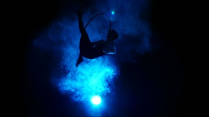 Aerial acrobat man on circus stage. Silhouette on a blue