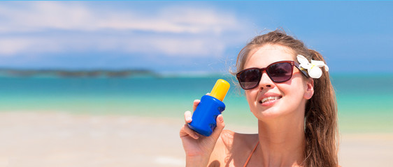 Young woman in sunglasses holding sun cream in hand