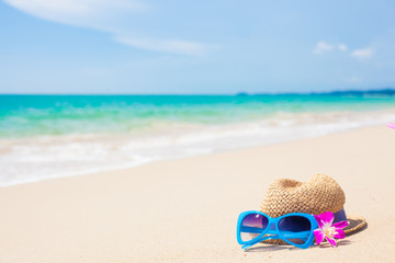 sunglasses and hat on tropical beach