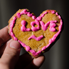 Hand made Valentine's Day cookie in the man's fingers