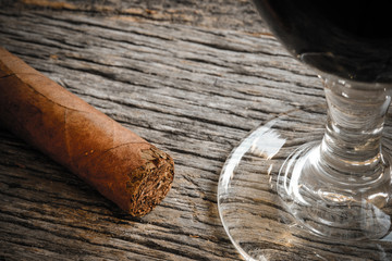 Cigar with Glass of red wine on Wooden Background