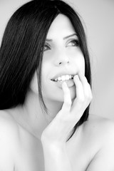 Portrait of beautiful woman posing naked touching lips smiling