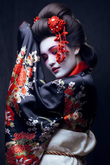 young pretty geisha in kimono with sakura and decoration