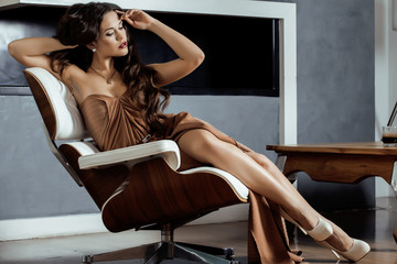 beauty yong brunette woman sitting near fireplace at home,