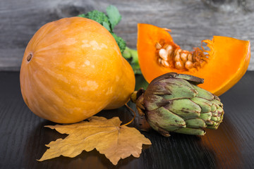 artichoke, sliced pumpkin and broccoli on  table.