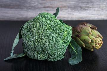 artichoke and broccoli on black wooden table.