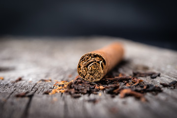 brown cigar  with tobacco leaves on grey wooden table
