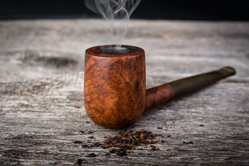 tobacco pipe  with smoke in wooden grey table.