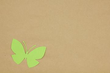 Cardboard butterfly on beige paper.