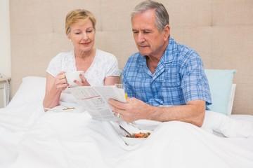 Senior couple having breakfast in bed