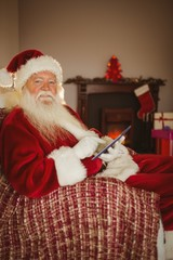 Cheerful santa touching tablet on the couch