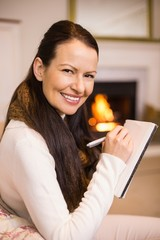 Smiling brunette sitting on the couch writing her christmas list