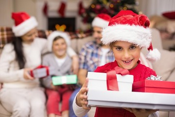 Festive daughter holding pile of gifts with his family behind