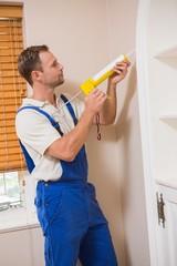 Man putting filling between door and wall