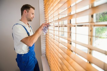 Handyman cleaning blinds with a towel
