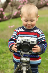 little boy with a camera in the spring park