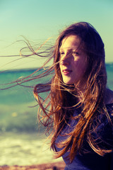 beautiful girl with long hair on the coast