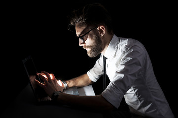 businessman at the computer that gives off light