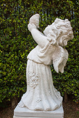 Cute cupid with bird, Cute little cupid statue with bird in the