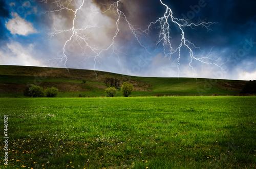 Leinwanddruck Bild Thunderstorm with lightning in green meadow.