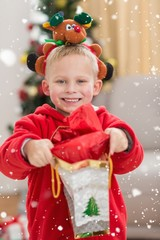 Festive little boy smiling at camera with gift