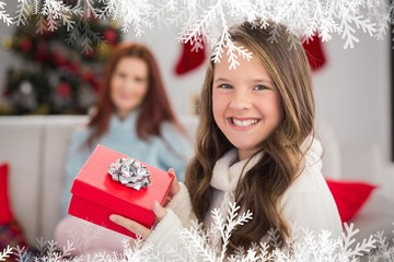 Composite image of festive little girl holding a gift