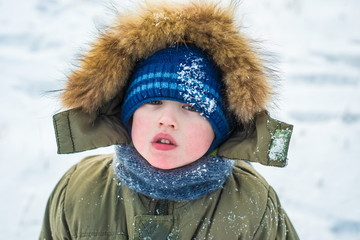 portrait of a little boy looking at the camera outdoors on backg