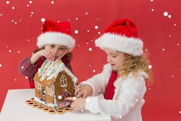 Festive little girls making a gingerbread house