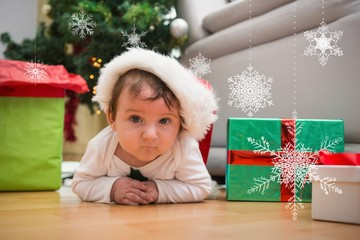 Composite image of cute baby boy lying on floor at christmas