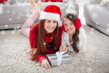 Composite image of festive mother and daughter smiling at camera