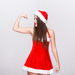 Sexy santa woman in hat showing biceps