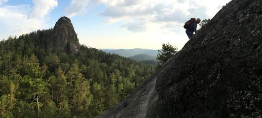 Мужчина скалолаз с рюкзаком на скале