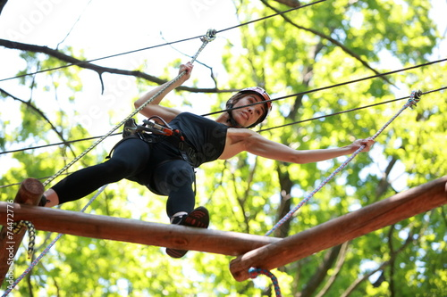 canvas print picture woman climbing in adventure rope park in safety equipment