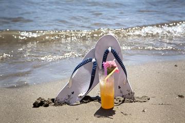 vaso con cocktail tropical  y chanclas en la playa